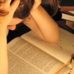 Garota debruçada sobre livros
