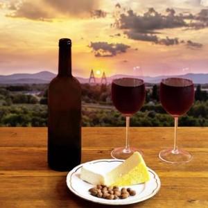 duas taças e uma garrafa de vinho com prato de queijo